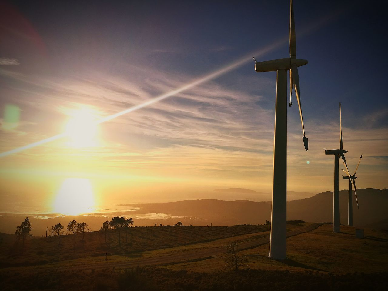 alternative energy, environmental conservation, sunset, fuel and power generation, wind power, wind turbine, renewable energy, field, sun, windmill, nature, sky, beauty in nature, no people, landscape, tranquil scene, industrial windmill, scenics, tranquility, sunlight, silhouette, rural scene, outdoors, technology, electricity, grass, day