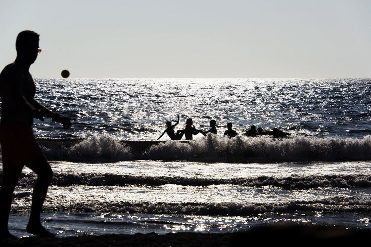 Silhouette of People playing, swimming in the waves in the island of Patmos, Greece in summer time Beach Beauty In Nature Horizon Horizon Over Water Land Leisure Activity Lifestyles Looking At View Men Motion Nature Outdoors People Real People Scenics - Nature Sea Silhouette Sky Standing Water Wave