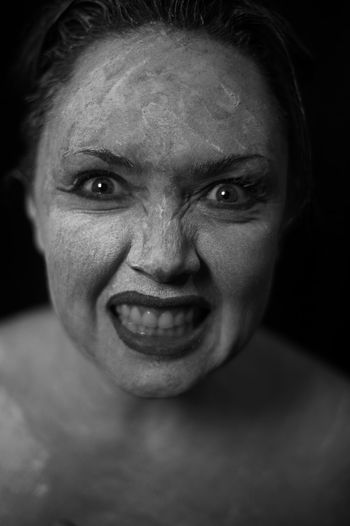 Close-Up Portrait Of Scary Woman With Face Paint Against Black Background