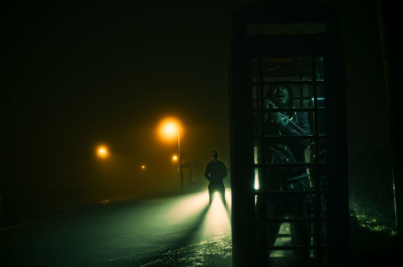 Man talking in telephone booth at night