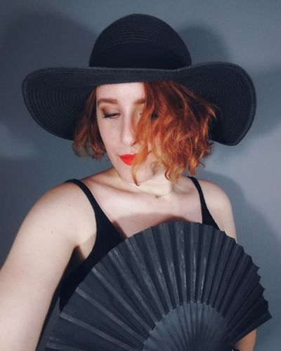 Beautiful woman holding hand fan and wearing hat against gray background