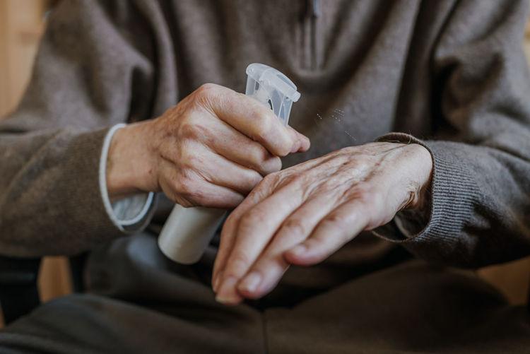 Midsection of man spraying sanitizer