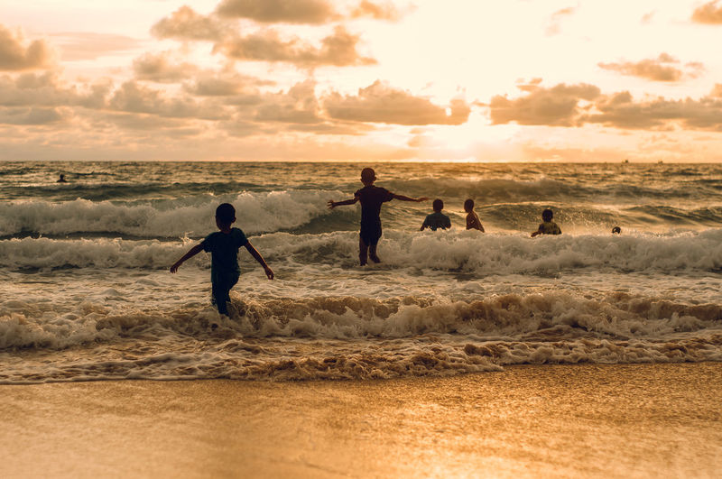 People enjoying on beach against sky during sunset