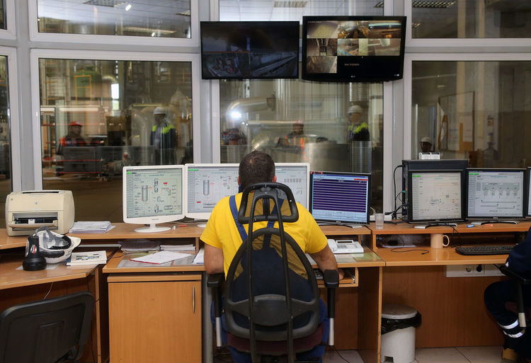 Rear view of people working in office