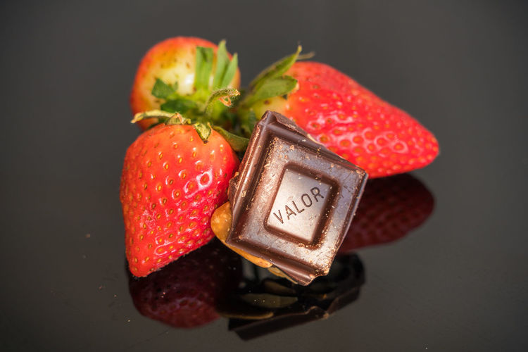 High angle view of strawberries on apple against black background