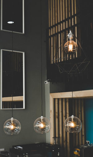 Low angle view of illuminated pendant light hanging on wall at home