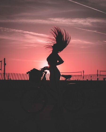 Silhouette Woman With Tousled Hair Standing Against Sky During Sunset