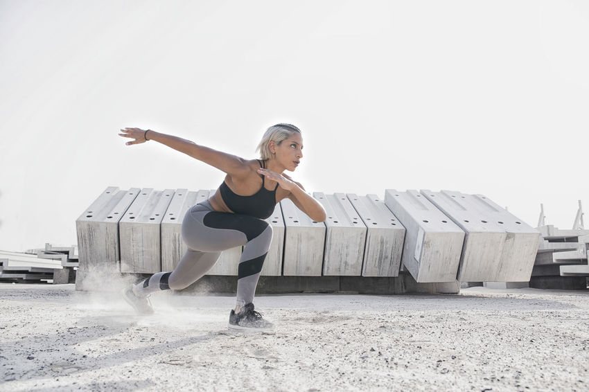 Middle Eastern Girl with short braided hair exercising on a dusty construction site wearing gray and black fitness outfit on a hot bright sunny day. Exercising Jumping Off Rocks Sitting Arms Outstretched Arms Raised Balance Bright Day Clear Sky Copy Space Day Dusty Fitness Model Full Length Hot Day ☀ Human Arm Leg Leisure Activity Lifestyles Middle Eastern Woman Nature One Person Outdoors Real People Sky Sports Clothing Stretching Vitality Women Young Adult Young Women