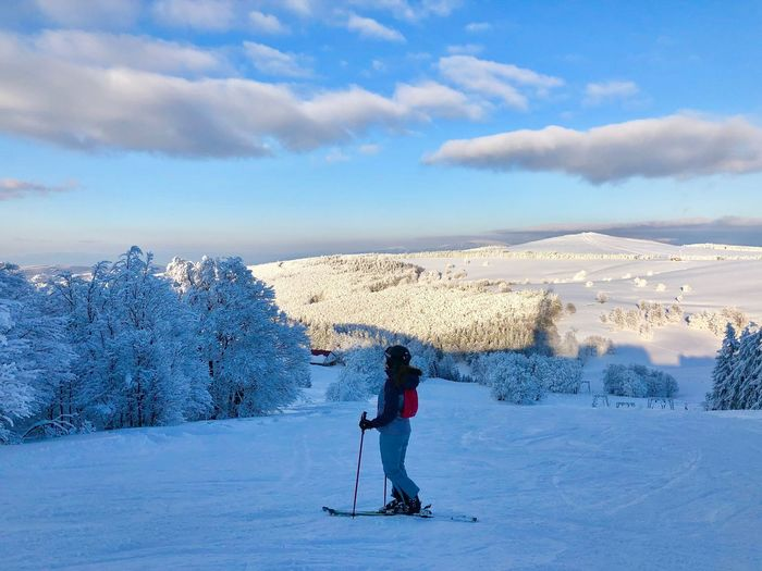 Woman skier on the slope surrounded by forest covered in snow Sunny Frozen WoodLand Trees Forest Activity Resort Slope Skier Sport Outdoors Snowcapped Mountain Snow Cold Temperature Winter Cloud - Sky Sky Leisure Activity Mountain Mountain Range Day Nature One Person Full Length Winter Sport Real People Beauty In Nature Lifestyles Skiing Warm Clothing