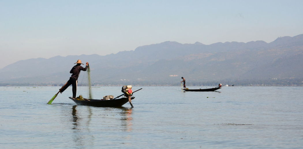 Men fishing while standing on boat in sea against mountains