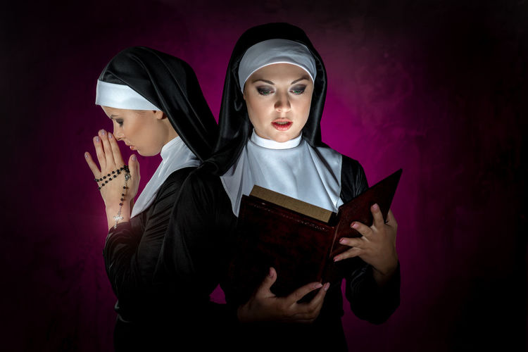 Beautiful young women reading bible and praying with rosary against illuminated black background