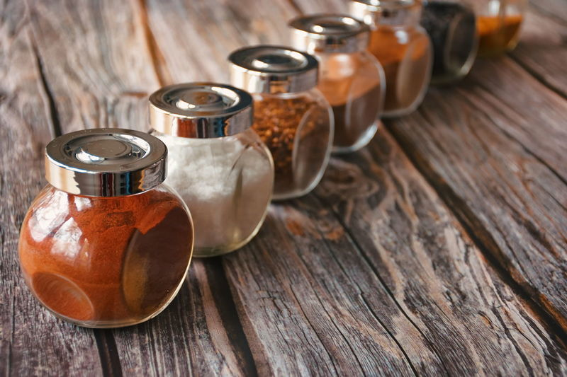 Various colorful herbs and spices in glass container on wooden background