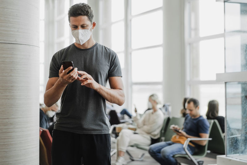 Man wearing mask using mobile phone at airport