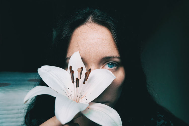 Adult Black Background Body Part Close-up Flower Flower Head Flowering Plant Front View Headshot Human Body Part Human Face Indoors  Leisure Activity Lifestyles Looking At Camera Obscured Face One Person Portrait Real People Women Young Adult Young Women