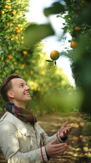 Real People One Person Smiling Young Adult Nature Happiness Outdoors Orange Tree Orange Fruits Autumn Summer Portrait Casual Clothing Juggling Fun Full Frame SONY A7ii Helios44 Green Garden Agriculture Orange Grove Healthy Eating Ecological