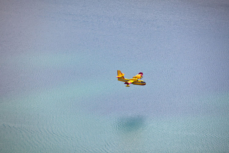 Firefighting plane above the water Above Activity Adventure Aircraft Airplane Day Extreme Sports FireFighting  Flight Flying Fun Leisure Activity Mid-air Nature Outdoors Over Plane River Sea Shadow Sport Transport Transportation Vacations Water