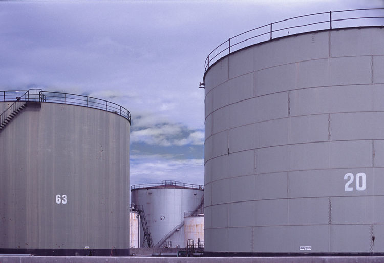 Low Angle View Of Oil Tanks Against Sky
