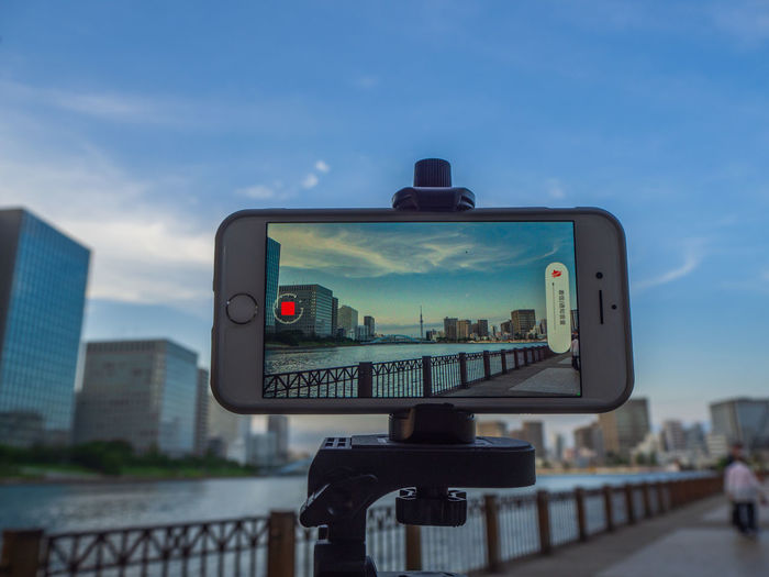 Close-up of camera against buildings in city