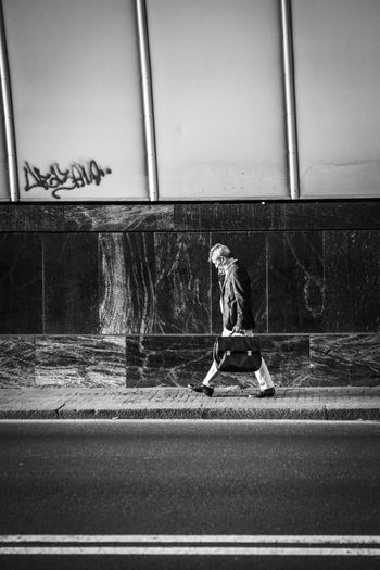 Side view of man walking on road against wall