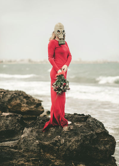 Woman wearing gas mask holding bouquet standing on rock at beach