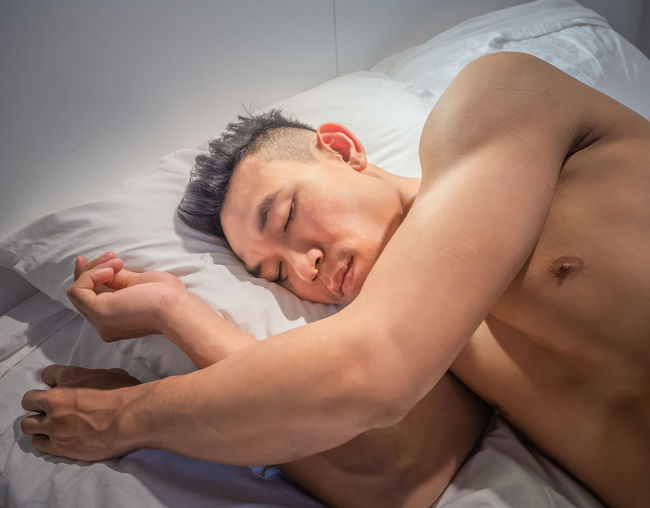 High angle view of man sleeping on bed at home