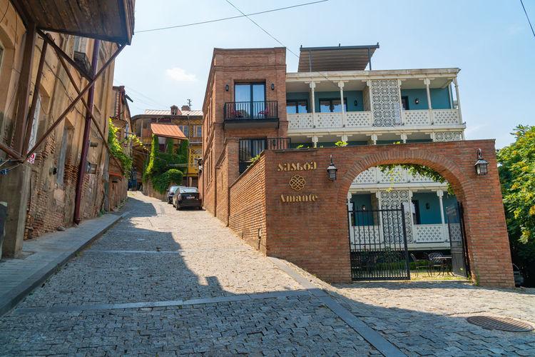Footpath amidst old buildings against sky