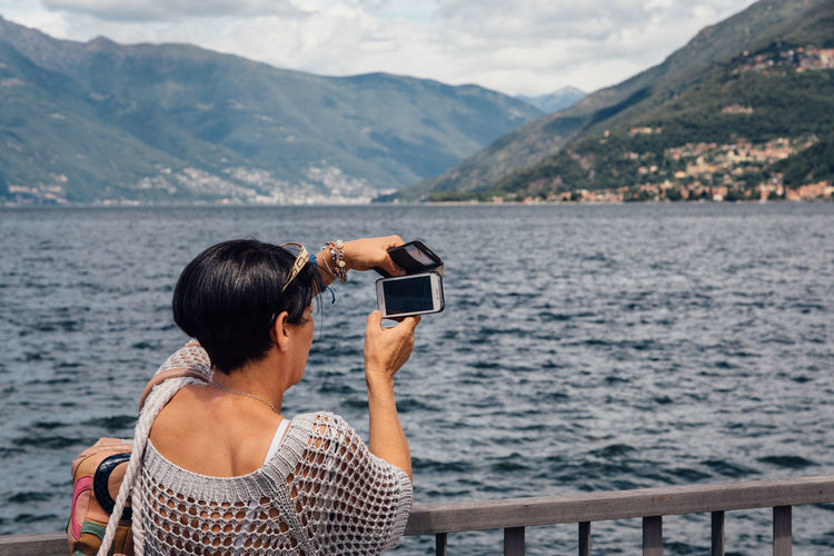 EyeEm Selects Photographing Rear View Sea Water Photography Themes Camera - Photographic Equipment Adults Only Holding Mountain Day Outdoors Travel Destinations Nature Scenics Beauty In Nature Adult Beach One Person Technology Wireless Technology One Woman Only Real People Tourist Taking Photos