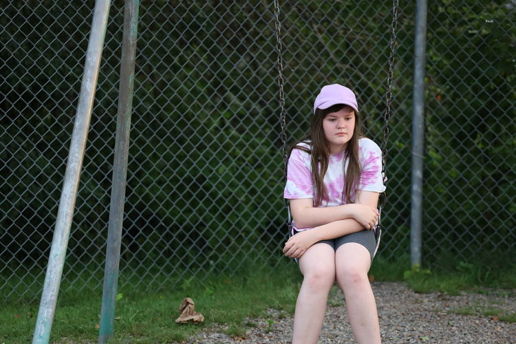 Thoughtful teenage girl sitting on swing