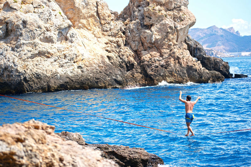 Man standing on rocks by sea