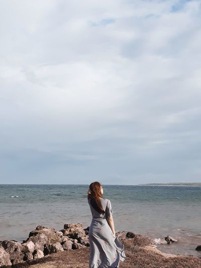 Rear view of woman standing on shore at beach against sky