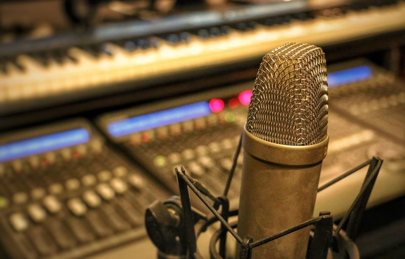 Close-up of microphone against sound mixer in recording studio