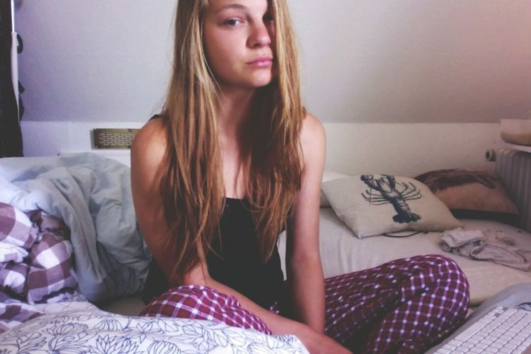 Beautiful young woman sitting on bed at home
