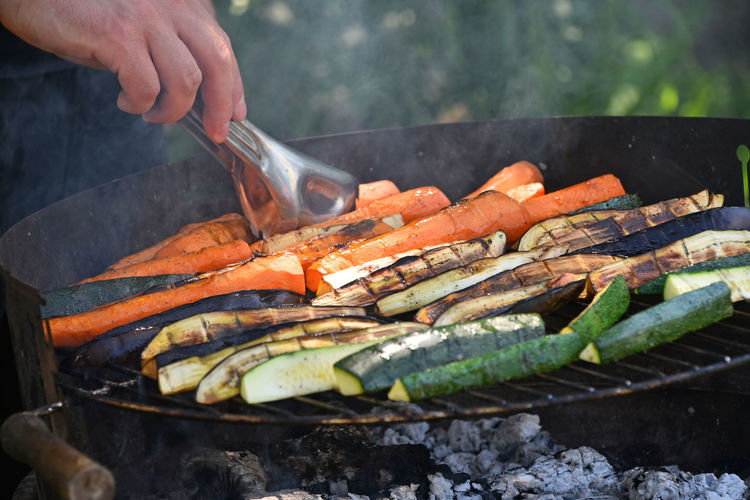 Cropped hand of man holding carrot in barbecue grill