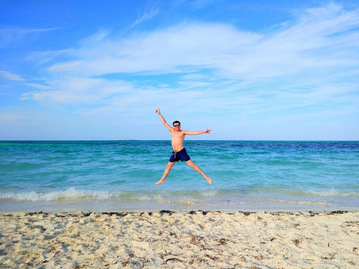 Man jumping on shore at beach against sky