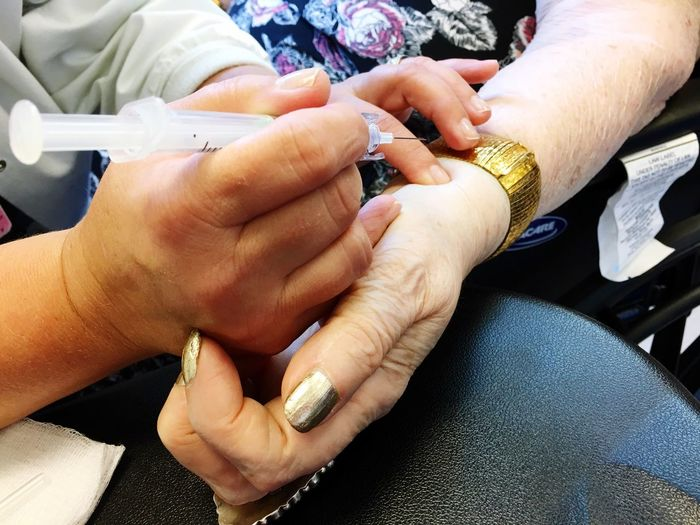 Cropped Image Of Doctor Injecting Senior Female Patient