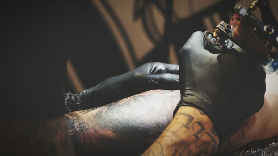 Close-Up Of Hands Making Tattoo On Man