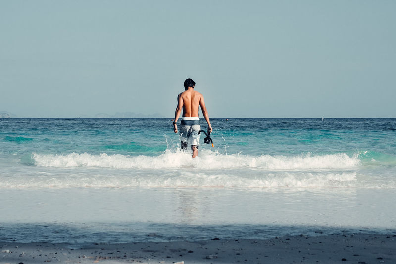 Rear view of man at beach against clear sky