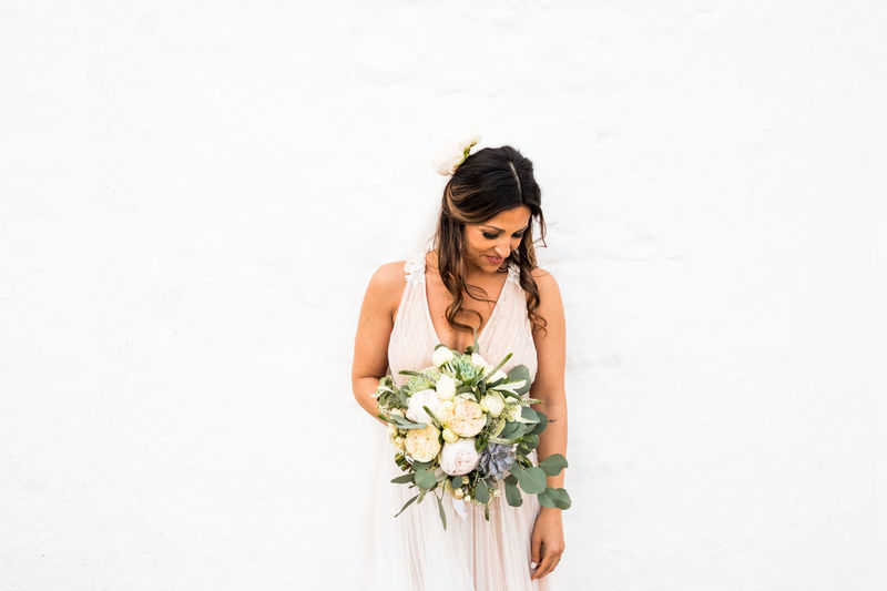 Young woman holding white flower standing against wall