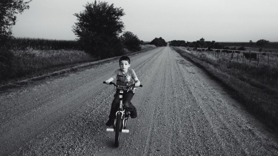 View of boy cycling on road