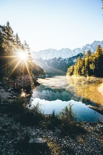 Early morning at lake Eibsee Mountain Range Bavaria Travel Roaming Sonyalpha Sky Water Beauty In Nature Sunlight Tree Nature Scenics - Nature Sun Tranquility Sunbeam Reflection Mountain Lens Flare Clear Sky Outdoors Tranquil Scene Lake