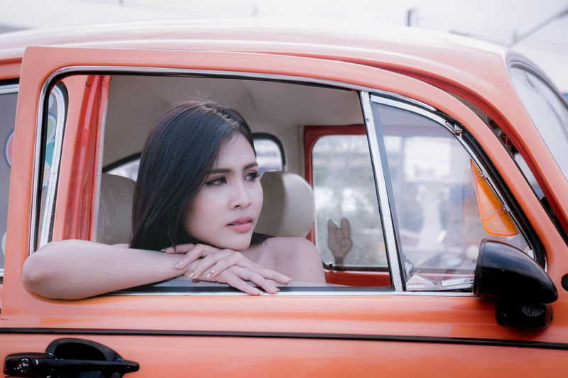 Close-up of woman looking through car window