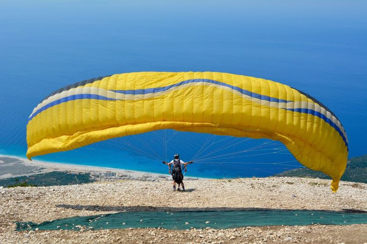 Boy with parachute against sea