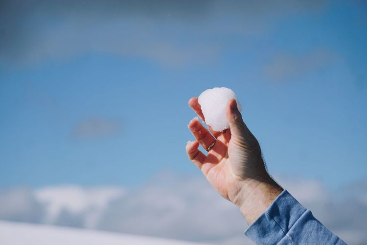 Close-up of person hand holding a snowball against sky