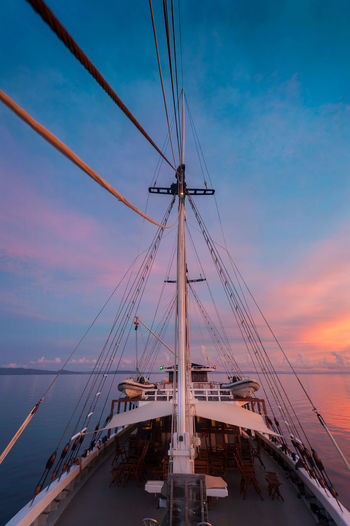 """Sailing in Raja Ampat, Indonesia. Aboard the traditional phinisi schooner, the """"Ombak Putih"""", sailing the Indonesian archipelago of Raja Ampat, West Papua. ASIA Cloud - Sky Colorful Cruise INDONESIA Mast Nautical Vessel No People Outdoors Phinisi Phinisi Boat Raja Ampat Remote Rigging Sailboat Sailing Sailing Ship Sea Ship Sky Southeast Asia Sunset Transportation Travel Vessel"""
