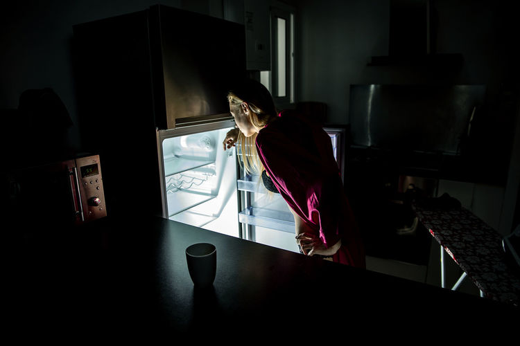 Rear view of woman looking into refrigerator at home