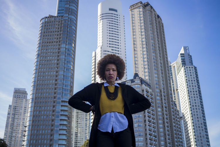 Low angle portrait of woman standing against modern buildings in city