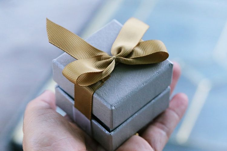 Close-up of hand holding paper in box