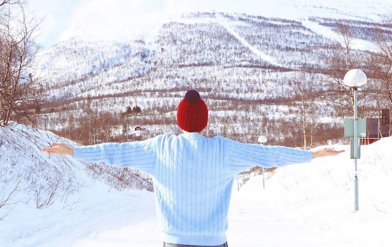Rear view of young woman with arms outstretched standing on snow covered field