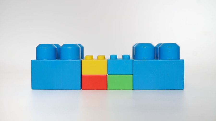 Close-up of blue toys on table against white background