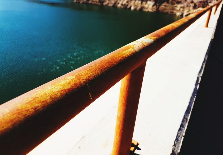 Close-up of railing by water
